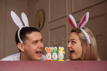 Happy Easter. Joyful couple with bunny ears looking at each other and smiling near rabbit toys at Easter day. Funny young family or friends at Easter sunday