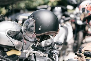 Vintage motorcycle helmet hanged on motorcycle in selective focus.