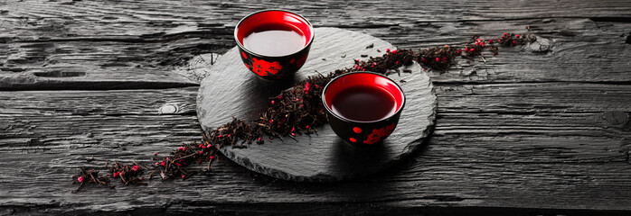 Cups of tea on slate plate on a black wooden table