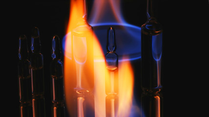 medical ampoules on fire. on a black background
