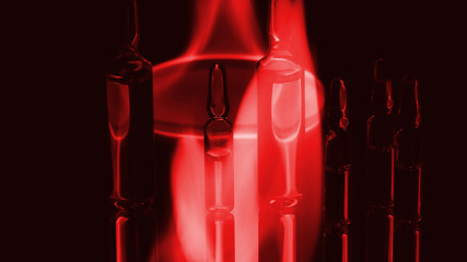medical ampoules on fire. on a black background. toned red fire.