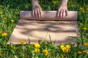 man rolling her mat after a yoga class on a green meadow on a summer sunny day, selective focus