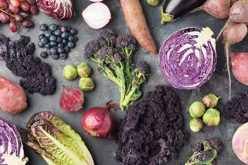 Vegetables and fruits background in purple, green and dark red colours, cabbage kale sprouts sweet potato onions broccoli blueberries grapes, top view, dark grey background, selective focus