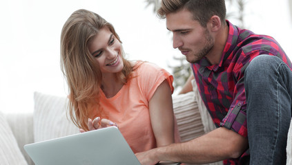 young couple is using a laptop and smiling while sitting on sofa at home
