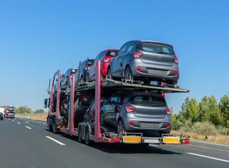 Car carrier trailer with cars on bunk platform. Car transport truck on the highway