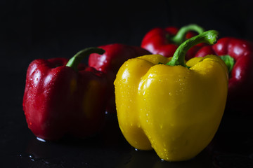 bell peppers yellow and red on black background