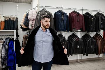 Stylish turkish man at the store of fur coats and leather jackets. Successful arabian beard man.