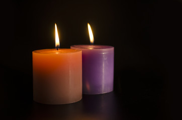 two big burning candles isolated on black