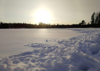 Snowy landscape from Finland. Sunset in the background. Miniature snowy mountains in front.
