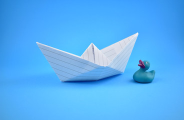 Paper boat stock images. Paper boat with duck. Paper boat on a white background. Blue background with boat
