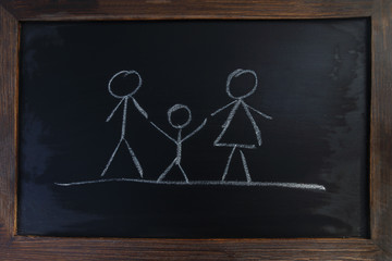 A family with parents and children drawn on a blackboard