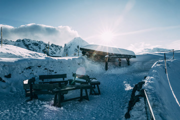 empty wooden benches in snow-covered mountains, mayrhofen ski area, austria