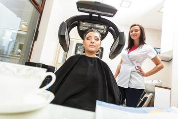 Woman in hairdresser, drying hair under machine