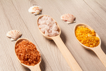 Spa nature products. Wooden spoons with brown, white and yellow sea salt for bathroom procedures
