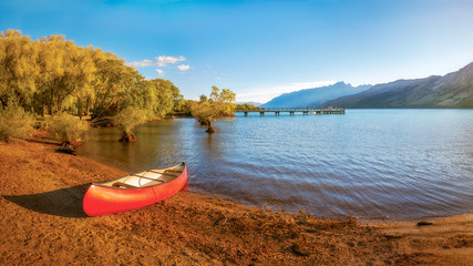 A canoe on the side of lake Wakatipu at Glenorchy Wharf close to sunset in New Zealand, South Island.