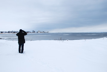 Man watching at an ice covered bay