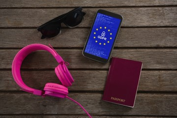 Composite image of headphones, sunglasses, passport and mobile