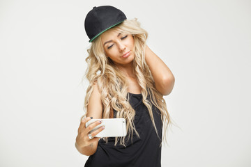 beautiful female with blonde long hair in cap and black t-shirt taking selfie on phone at white background. isolated self-portrait.