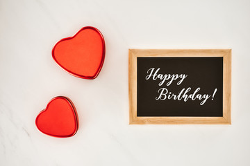 top view of blackboard in frame with HAPPY BIRTHDAY lettering with heart shaped isolated on white