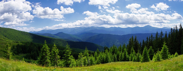 Panoramic view of wooded hills and blue sky with white clouds.