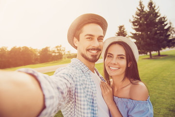 Portrait of cute romantic bearded brunet guy in shirt, bonding dreamy lady, take shot, make memories. Leisure, chill happiness, lawn stroll, relax, romance lifestyle, well dressed partners posing