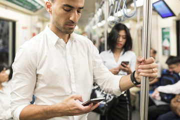 Businessman and businesswoman using cell phones in the subway