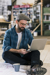 Smiling man with laptop and construction plan sitting on the floor