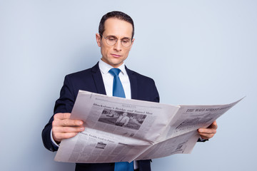 Portrait of focused concentrated strict minded confident respectable proud freelancer having a rest reading the latest news holding newspaper isolated on gray background copy-space