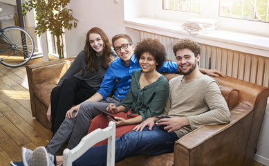 Portrait of smiling young people sitting on sofa with tablet