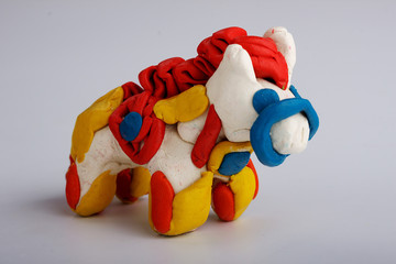 A horse made of plasticine on a homogeneous background