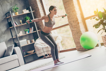 Low-angle photo of sportive strong active attractive purposeful ideal woman with excellent body figure doing exercise with lifting green dumbbells at home in front of tv in sun glare, sunlight