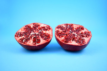 Juicy pomegranate stock images. Pomegranate on a blue background. Juicy pieces of pomegranate. Split pomegranate