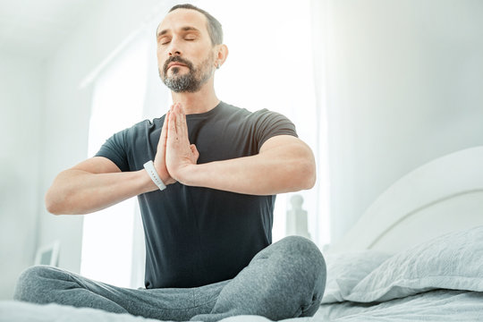 Find yourself. Calm healthy occupied man sitting in the bright room on the bed holding hands opposite his body closing his eyes.