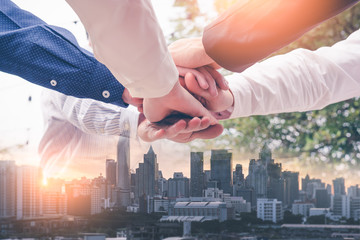the double exposure image of the many businessmen take a hands together during sunrise overlay with cityscape image. The concept of agreement, business, cooperation, partnership and successful.