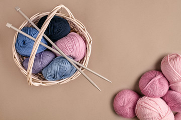 Different colored yarn in basket with knitting needles. Top view