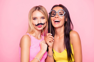 Close up portrait of two crazy funny cheerful comic attractive beautiful girlfriends wearing summer clothes and having fun using fake mustache and eyewear, isolated on bright pink background