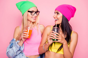 Close up portrait of two cheerful delightful lovely cute funky girlfriends wearing bright vivid colorful clothes, they are laughing and drinking cocktails, isolated on pink background