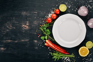 The background of cooking. Plate with fresh vegetables. On a wooden surface. Top view. Copy space.