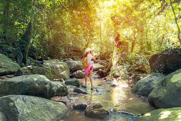 Asian traveler photographer women taking a photos of waterfall in deep forest in Thailand. Travel Concept.
