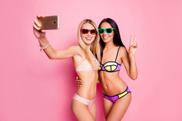 Pretty, seductive, charming blonde, stylish brunette, trendy tourists, ladies in swim suits  shooting self portrait and showing v-sign, hugging, embracing, standing over pink background