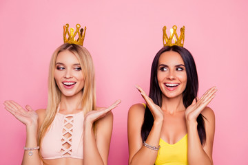 Nice, charming, perfect, smiling, excited, blonde, brunette girls with small gold crown on heads, holding arms, palms near face, looking to each other with eyes over pink background