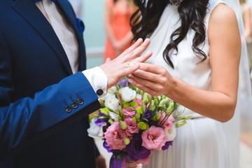 Bride Putting on Wedding Ring on Groom