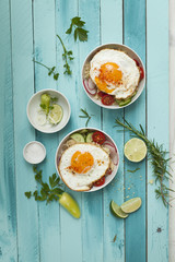 cous cous bowl with vegetables and fried egg on a turquoise wooden background