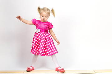 Little girl 3 years old in a red dress with bows in her hair. Beautiful girl in a beautiful fluffy dress posing against a white wall.