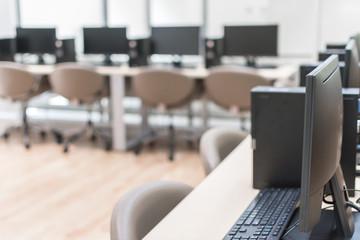 Computer lab blur background with pc desktop computer machine in blurry school class or office desk workspace