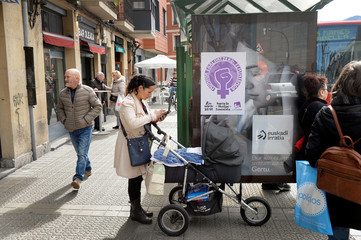 A woman stands at a bus stop with a push chair alongside a poster announcing a feminist strike, ahead of Thursday's International Women's Day, in Bilbao