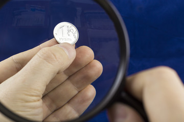 Watching one ruble coin through magnifying glass in the man's fingers on the dark blue background.
