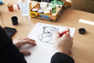 Ребенок на уроке рисования рисует картину