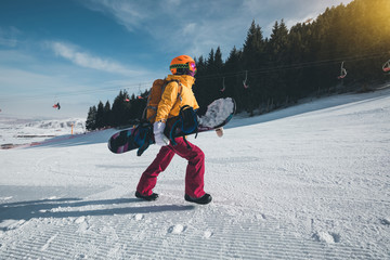 woman snowbaorder with backpack ascent on winter mountains