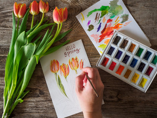 the hand of the artist on the picture with the tulips and the words Hello spring